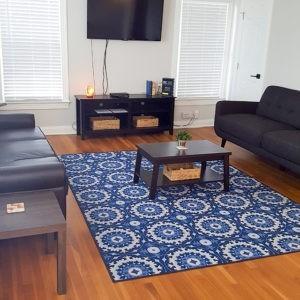 Living room photo with hardwood floors, leather furniture, coffee table, flat panel, windows and plants